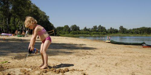 Spelen op het zandstrand bij het recreatiemeer op camping de Kienehoef